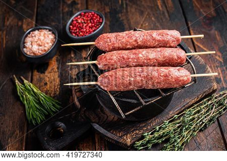 Raw Kofta Or Lula Kebabs Skewers On A Grill With Herbs. Dark Wooden Background. Top View