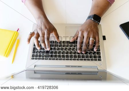 A Male Hands On The Laptop Keyboard. Top View An African-american Guy Is Typing Email, Programmer Is