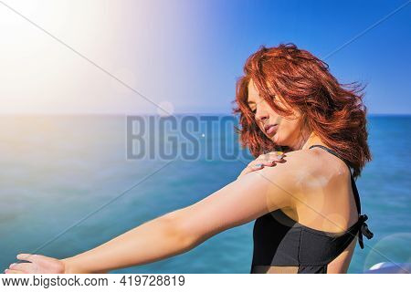 Woman Putting On Sun Protection Lotion On Arm. Red-hair Girl Tanning Using Sun Block Body Cream On S