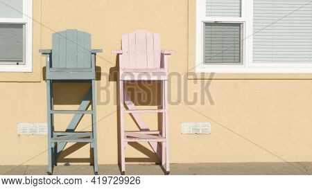 Two Vintage Wooden Lifeguard Chairs By Yellow Wall, California Usa. Empty Life Guard Retro High Seat