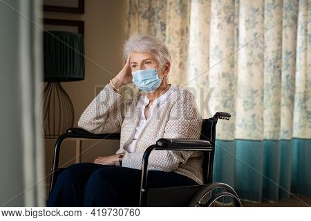 Sad senior woman sitting on wheelchair and wearing a face mask for safety against coronavirus, alone at home. Depressed old disabled woman on wheelchair with headache at nursing home feeling lonely.