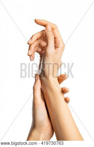 Close up of silky female hands isolated against white background. Female gentle hands with slender fingers. Closeup of beautiful woman manicure on nails: softness and skin care concept.