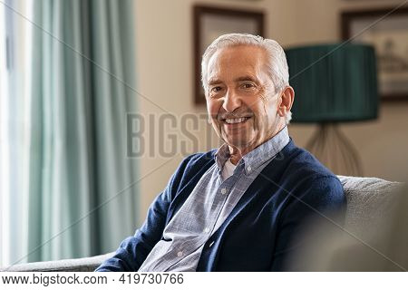 Portrait of happy senior man smiling at home. Old man in casual relaxing on sofa and looking at camera. Portrait of elderly man enjoying retirement at nursing home.