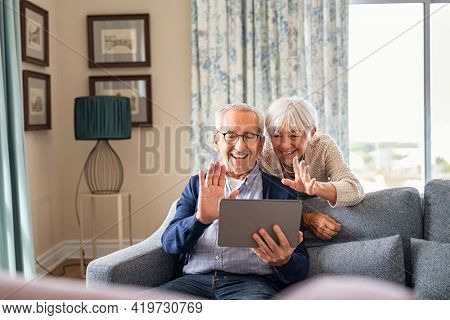 Happy senior couple using digital tablet for video conference and waving hand. Old man and smiling wife using digital tablet for video call with nephews or friends.