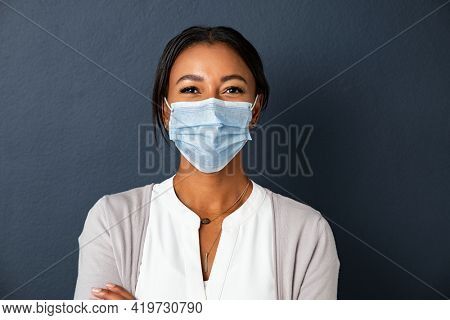 Beautiful young mixed race woman wearing protective face mask isolated against grey wall with copy space. Portrait of smiling indian woman wearing surgical mask due to coronavirus, positive attitude.