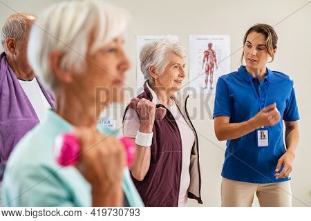 Group of old happy people using dumbbells for workout session with physiotherapist. Group of senior man and elderly woman exercising with dumbbells in clinic with trainer. Seniors doing workout.