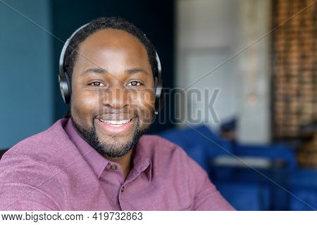 Call Center Operator Wearing Headset Looks At The Camera With Cheerful Smile, Headshot Of Cheerful A