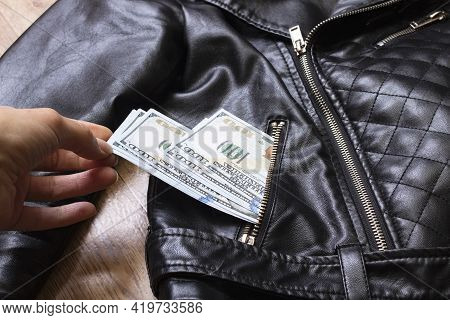 Hand Pulls Dollars Out Of Jacket Pocket Close Up