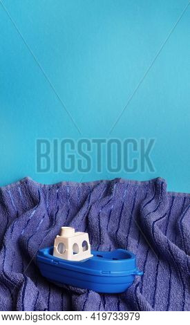 Ship toy on blue towel waves abstract concept photo of turbulent sea or ocean on blue copy space background