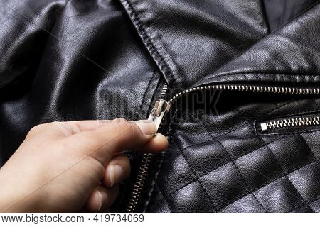 Hand Unbuttones The Lock Of A Black Leather Jacket