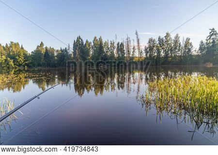 Serene Fishing In The Evening In Summer On A Quiet River With A Long Rod From The Shore.