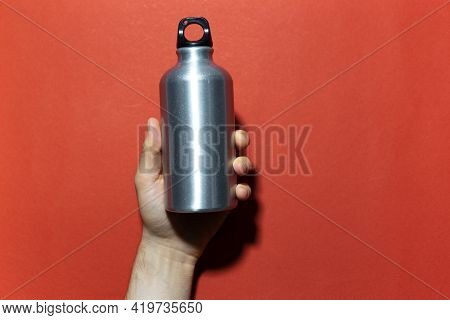 Close-up Of Male Hand Holding Reusable Aluminum Thermo Water Bottle On Background Of Red Textured Wa