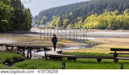 Woman Walking On A Wooden Path Across A Swamp In Shoreline Trail, Port Moody, Greater Vancouver, Bri