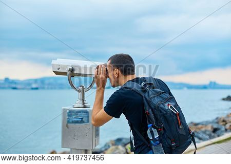 A Tourist Guy With A Backpack On His Back Looks Through The Sightseeing Binoculars On The Observatio