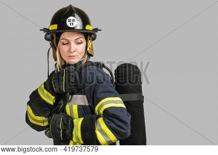 Young Caucasian Woman In Uniform Of Firefighter Posing In Profile With Air Tank On Her Back Isolated