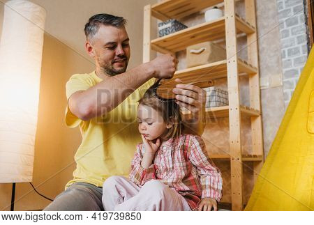A Caring Father In A Yellow T-shirt Combs His Little Daughter's Hair While Sitting On The Floor At H