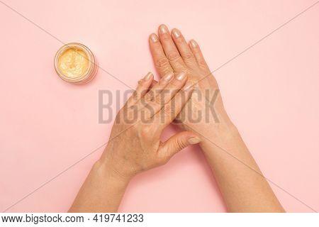 Woman Applying Cosmetic Cream On Her Hands. Female Elderly Hands. Skincare. Senior Woman. Pink Backg