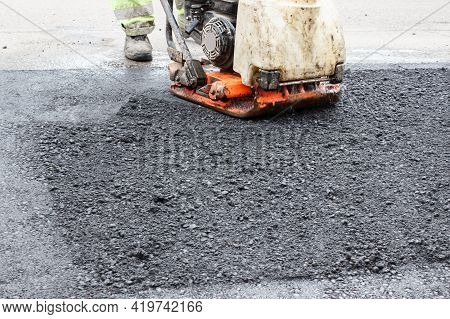 Worker Ramps The Asphalt On The Road With A Mechanical Rammer. Laying The Road Surface. Hot Asphalt