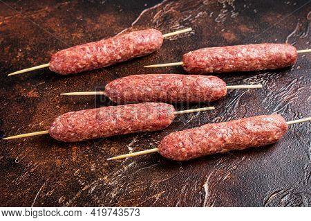 Raw Kofta Meat Kebabs Sausages On Skewers. Dark Background. Top View