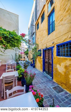 Street cafe in scenic picturesque streets of Chania venetian town with coloful old houses. Chania greek village in the morning. Chanica, Crete island, Greece