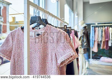 A Hanger With Clothes Near A Large Window. Lots Of Fashionable Stylish Clothes.
