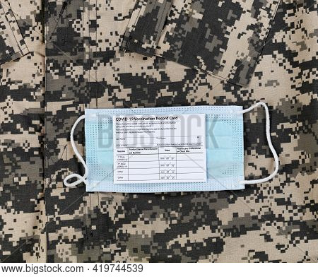 Covid 19 Vaccination Record Card And Personal Facemask On Military Uniform.  Individual Record For U