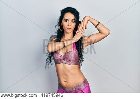 Young indian woman wearing traditional belly dancer costume. Dancing exotic oriental dance with body and hands