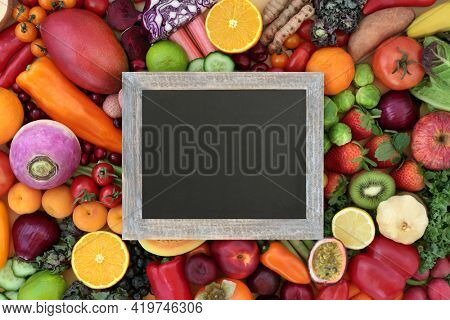 Plant based healthy natural antioxidant food with fruit and vegetables that neutralise free radicals also high in fibre, anthocyanins, lycopene, vitamins, and carotendoids. Copy space on blackboard.
