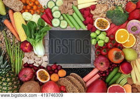 Plant based high fibre health food for vegan diet with fruit, vegetable, legumes, grain products and cereals. High in antioxidants, omega 3, vitamins,  anthocyanins and smart carbs with blackboard.