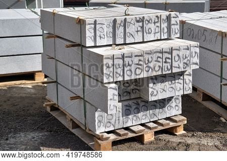 Concrete Curbs On Wooden Pallets Stand On The Street During Street Repair.
