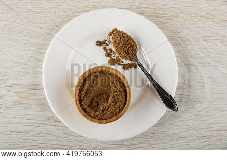 Bamboo Bowl With Ground Cinnamon, Spoon With Cinnamon In White Plate On Wooden Table. Top View