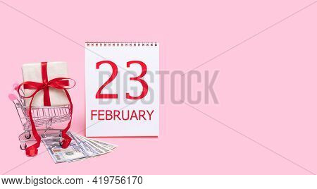 23rd Day Of February. A Gift Box In A Shopping Trolley, Dollars And A Calendar With The Date Of 23 F