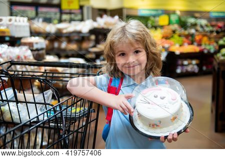 Child With Shopping Basket Purchasing Cake In A Grocery Store. Customers Kid Buying Sweets At Superm