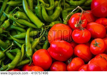 Tomatoes And Pepper Background. Fresh Tomatoes And Green Chilli Pepper Variety Grown In The Shop. To