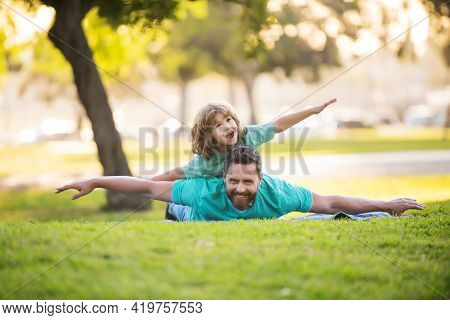 Childhood And Parenthood Kids Concept. Happy Father And Son Playing Together Outdoor. Concept Of Fri