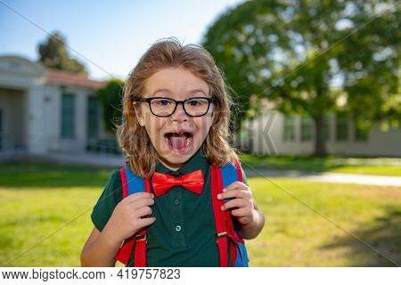 Portrait Of Excited Pupil With Backpack Near School Outdoors.