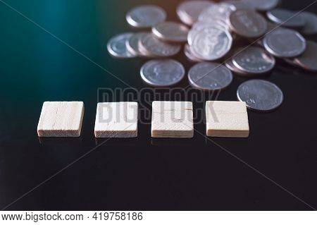 Square Wooden On Black Glass With Blur Image Of Stack Cash Coin Money Background. For Add Text Happy