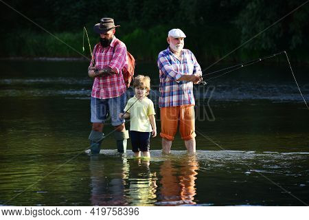 Fly Fishing For Trout. Senior Man Fishing With Son And Grandson. Fishing Became A Popular Recreation