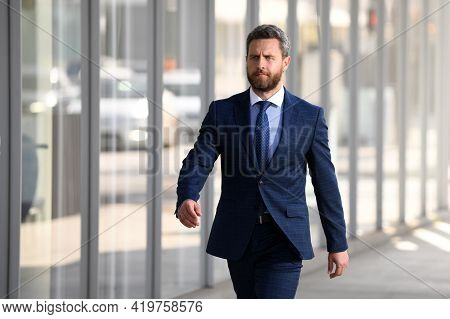 Businessman Walking Outside Business Centre. Portrait Of A Confident Young Business Man Walking In T