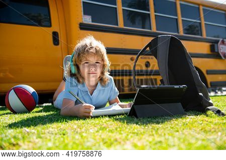 Child Pupil Does School Homework Laying On Grass In The Park Near School Bus. School Kid Outdoor.