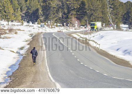 An Athlete In A Dark Tracksuit Runs Along The Side Of The Road, The Track Against The Background Of