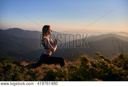 Side View Of Brunette Practicing Yoga In Warrior Pose. Female Is Meditating In The Mountains After S
