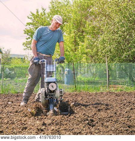 A Man Cultivates The Soil In The Garden Using A Motor Cultivator - Tiller