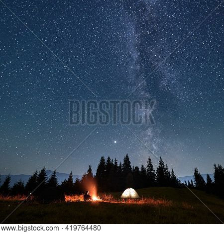 Male Traveler Looking At Campfire While Sitting Near Camp Tent Under Beautiful Night Sky With Stars