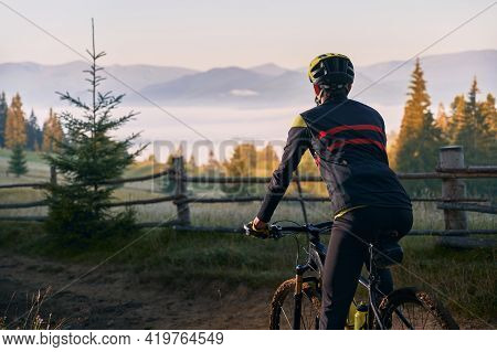 Cropped Back View Of Male Cyclist In Cycling Suit Standing With Bike With Hills On Background. Man B