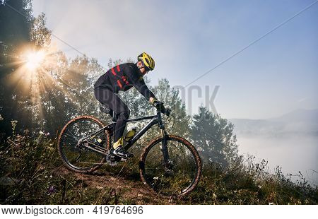 Horizontal Snapshot Of Man Riding His Bike In The Mountains In Early Foggy Morning Going Downhill. S