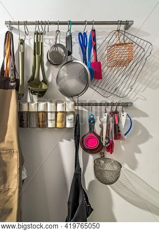 Metal Rail With Kitchen Tools, Kitchen Utensils Hanging, Apron And Seasoning In Front Of A White Wal