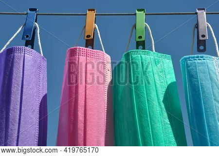 Front View Of Multi Colored Surgical Face Mask (disposable Mask) Hanging On Clothesline Wire With Cl