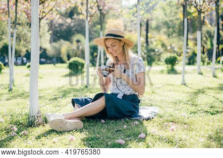 Young Beautiful Woman Photographer In A Hat With A Digital Camera In A City Park. Portrait Of A Smil