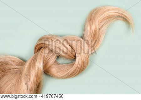 Blonde Hair Lock Tied In Knot. Strand Of Honey Blonde Hair On Mint Background, Top View. Hairdresser